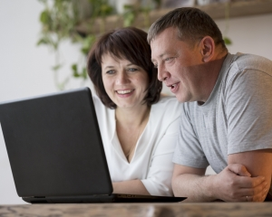 A woman and a man sit in front of a laptop, looking at the screen and smiling.
