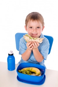 Smiling boy eating sandwich with a blue plastic lunchbox containing a banana and some grapes and a blue plastic water bottle