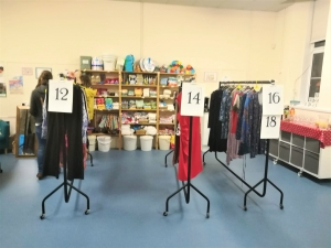 Rails of clothes separated into different womens sizes at a clothes swish at Marpool Primary School
