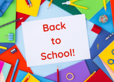 """School workbooks of assorted colours arranged in a ring, with various pieces of stationery dotted around the workbooks. A piece of paper in the middle of the workbooks with """"Back to school!"""" written on it."""