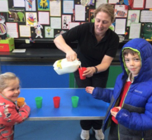 Keri Lambert, school dinner assistant at Georgeham Primary School pouring milk for pupils at Devon's first Plastic Free School