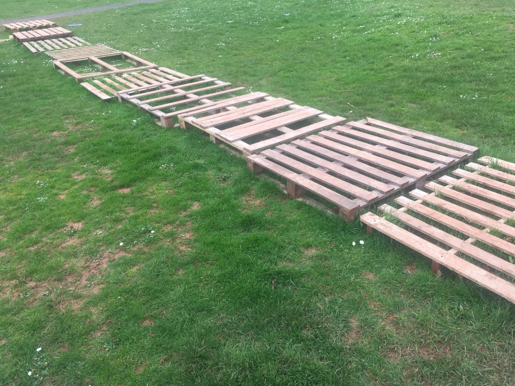 a pathway made of pallets across grass at Whipton barton loose parts play