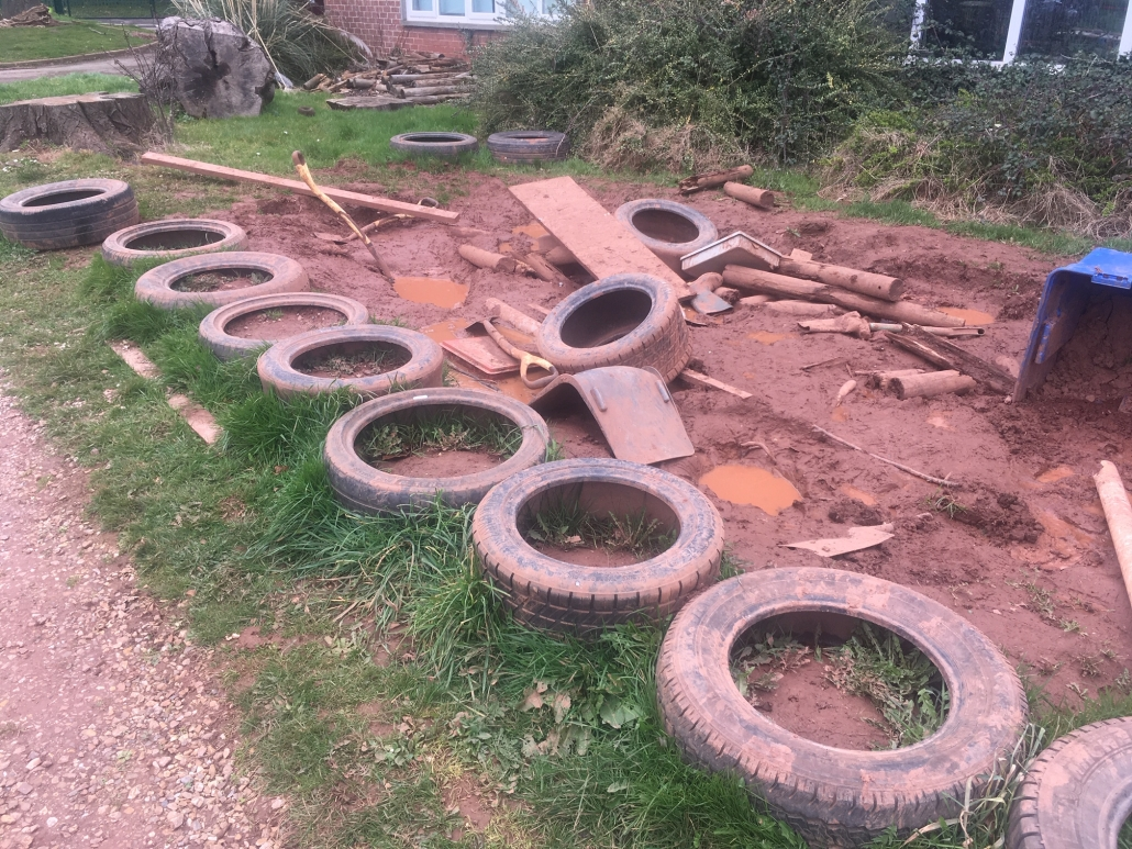 Tyres, spades and other assorted items lying in mud for loose parts play at Whipton Barton Primary school