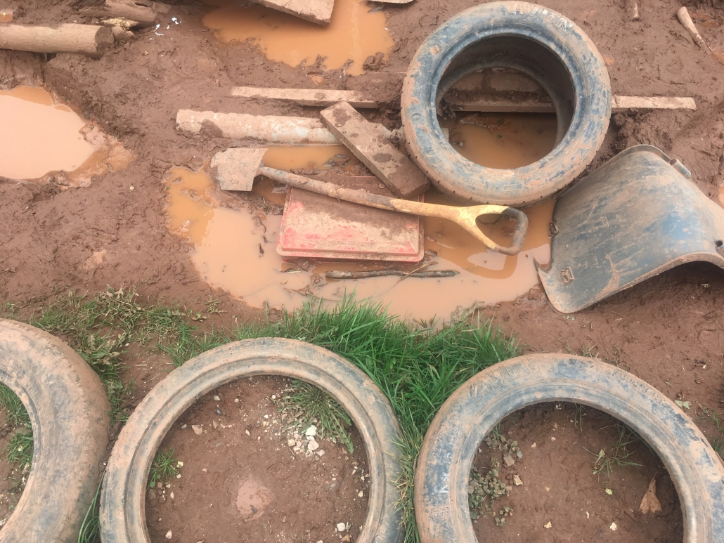 Assorted items like a spade, plastic chair seat, planks and tyres lying in muddy piles for loose parts play at Whipton Barton Junior School