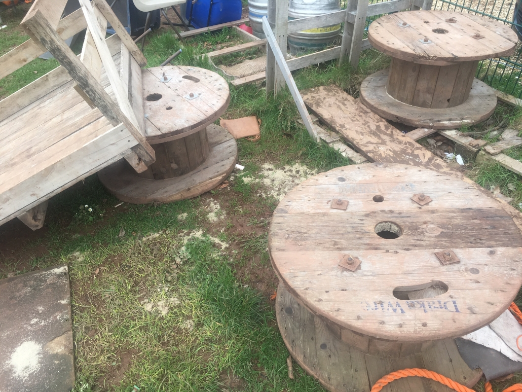 Pile of mixed wooden loose parts play equipment at Whipton Barton Junior School including large cable reels and pallets.
