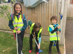 3 children in Scout, Cub and Beaver uniforms with litter pickers
