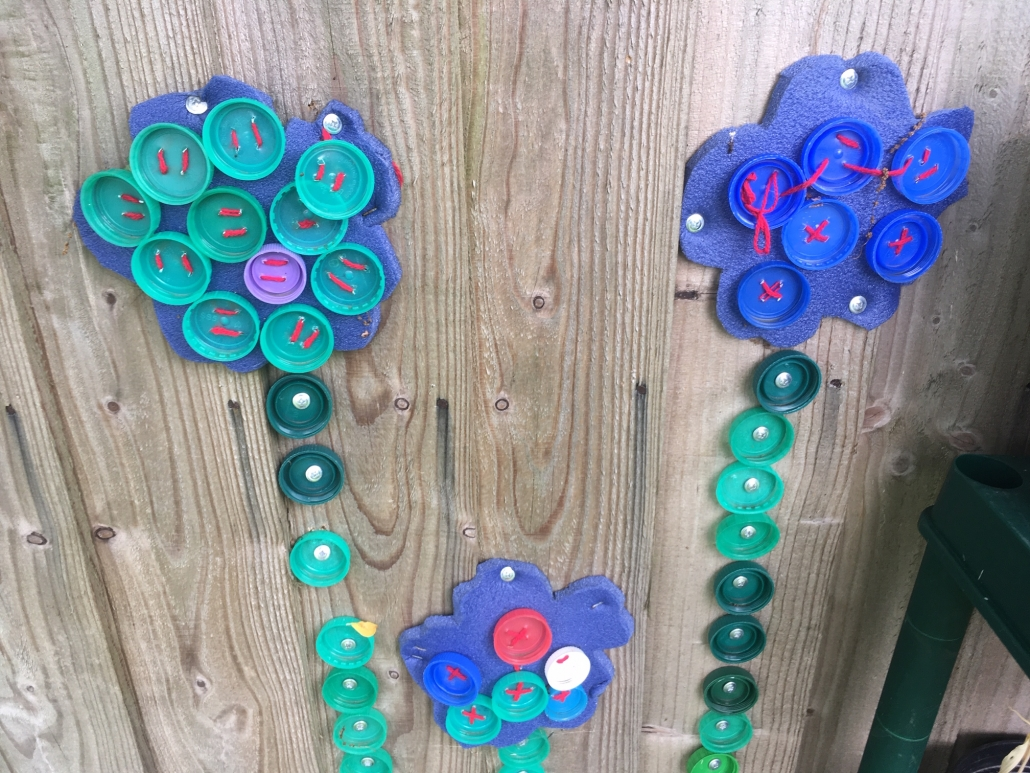 flower sculpture on wall made from repurposed milk bottle tops at Holsworthy Primary School
