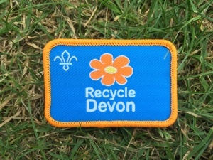 Close up of a Recycle Devon Scout Badge lying on grass