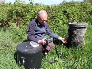 An Inspector using monitoring equipment to measure gas from a redundant landfill site