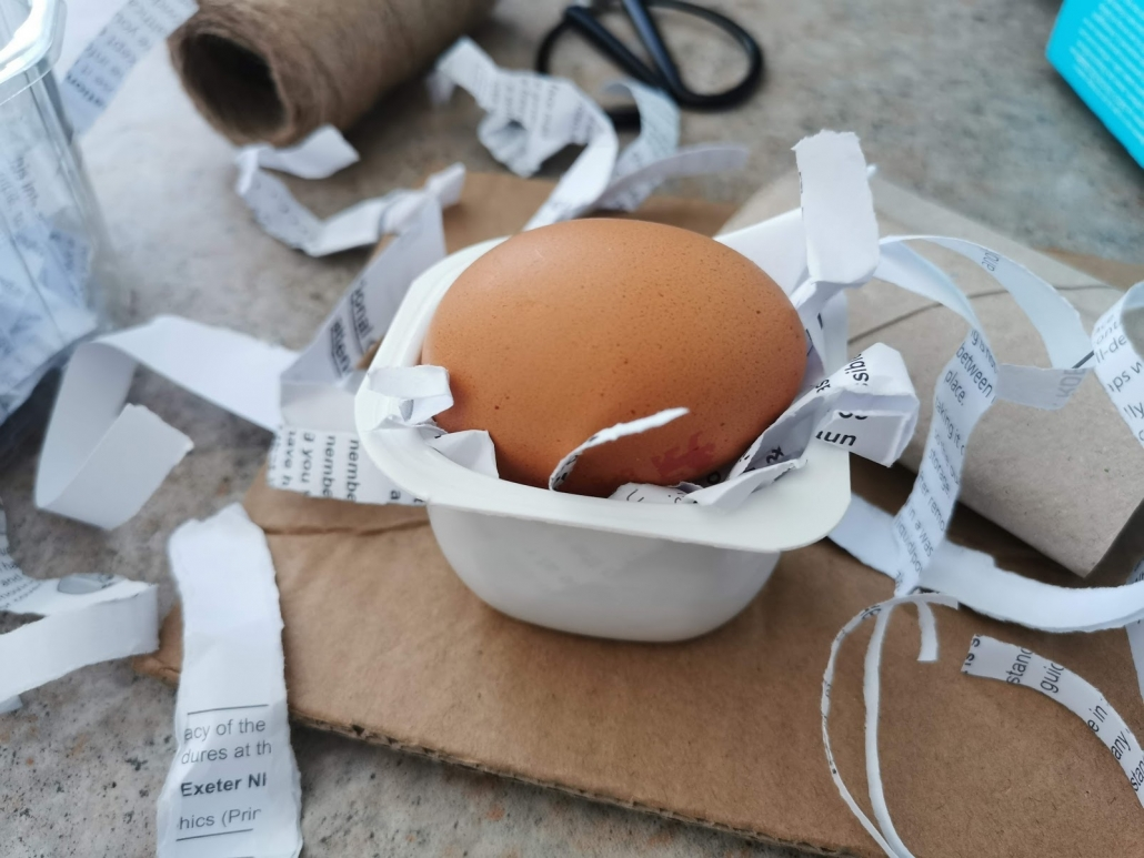An egg rests in a yogurt pot filled with shredded paper. There are various recyclable materials in the background of the image, including cardboard along with scissors and string.