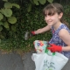 Girl picking up litter from a hedge wearing gloves