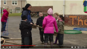 Still from video of children in coats playing outdoors with adult play supervisor