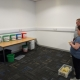 Two visitors from ROC creative holding beanbags, looking at five coloured buckets placed on a table.