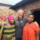 Annie in Tanzania smiling between two of her hosts in front of a house