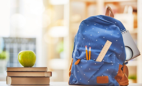 A stack of three books with a green apple on top, next to a blue spotted school rucksack, with two pencils and a ruler sticking out from the pocket.