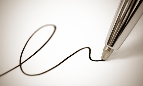 Close up image of a ballpoint pen nib signing a piece of paper