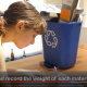 A young girl weighing and recording the weight of cardboard in a blue recycling bin