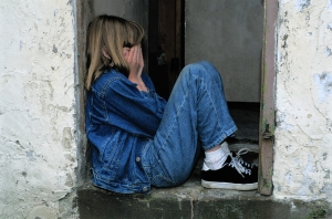 Young girl sitting in a doorway with her hands over her face