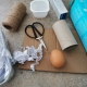 An egg is surrounded by empty cardboard packaging, a yogurt pot, a fruit punnet, shredded paper, scissors and string.