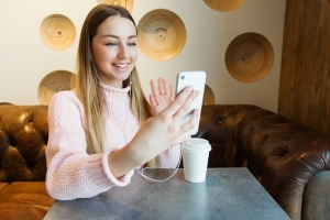 A young woman wearing earphones is sitting at a table with a coffee cup. She holds her phone up to her face and smiles at the screen and waves.