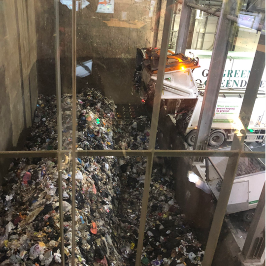 A picture of the waste bunker at Exeter Energy from Waste plant with a lorry unloading rubbish into the pit (through glass)