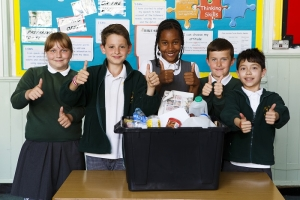 5 smiling children in school uniform standing behind a recycling box full of clean recyclable household packaging