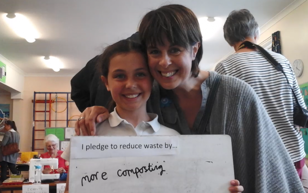Child and parent holding up a pledge at St Peters Primary School Eco Fair