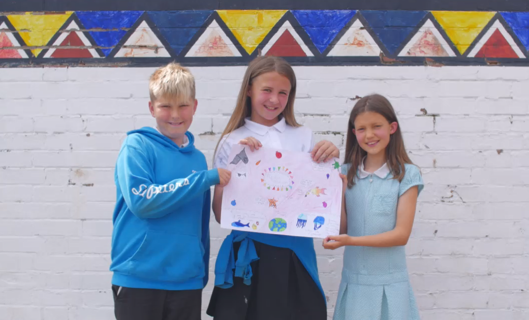 Smiling children holding up a poster