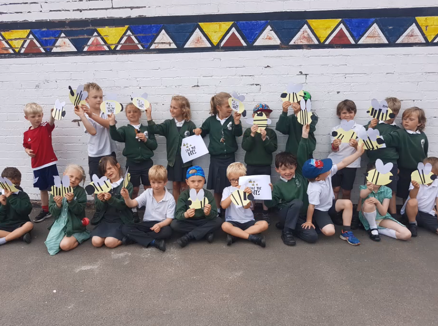 Group of children at St Peters Primary School in Budleigh Salterton standing and sitting showing off their bee pictures and posters
