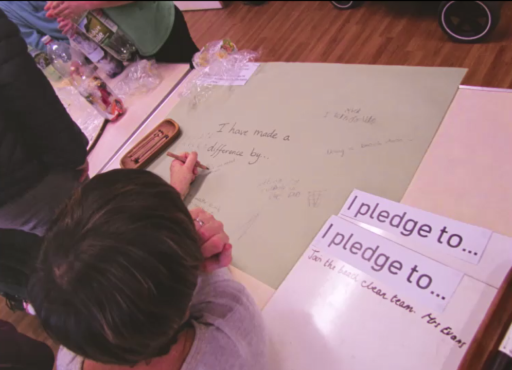 """parent writing on a large sheet of paper saying """"I have made a difference by..."""" beside a sign saying I pledge to"""