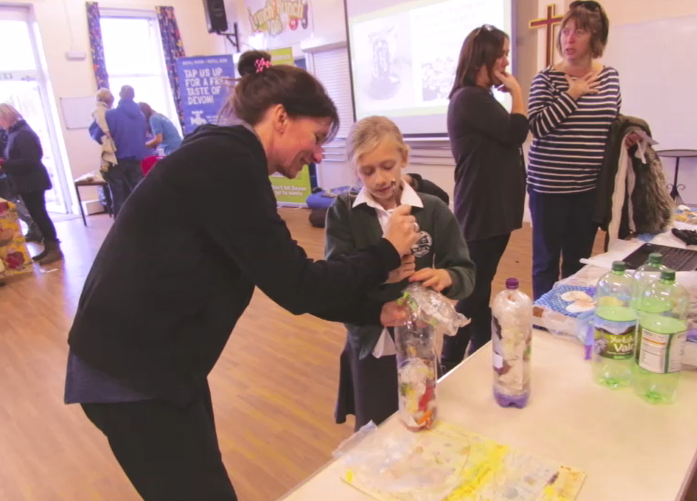 Pupil being shown how to make an Eco-Brick at st Peter's Primary School Eco-Day