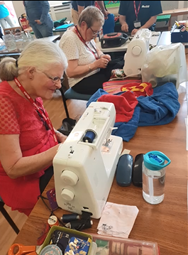 Picture of two ladies sat at sewing machines demonstrating mending items at Repair Cafes