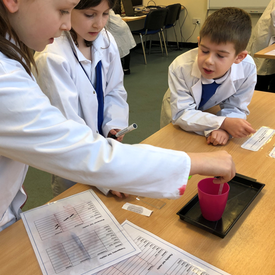 Pupils carrying out a science experiment looking at properties of materials at Pinbrook Recycling Centre