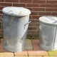 Two simple metal dustbins on a patio.