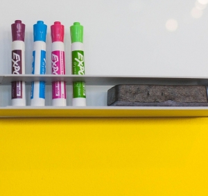 Close up of whiteboard with coloured whiteboard pens and board rubber